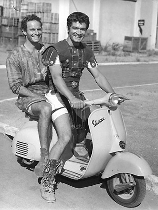 "Charlton Heston tooling around in costume on the ""Ben-Hur"" Cinecitta set at on a Vespa, 1959"