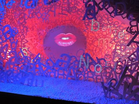 Video artist Bertrand Planes dresses the Bon Marche Paris holiday windows with a one with a pair of lips singing a rock n' roll Christmas surrounded by a pile of big white letters