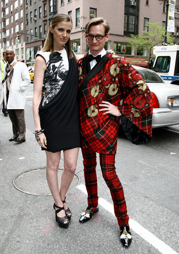 Barneys New York's Amanda Burton outside the store event with Hamish Bowles wearing Alexander McQueen Embroidered tartan cape, white shirt, black waistcoat, tartan trousers and bow tie (AW06)
