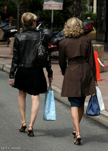 Two women with shopping bags walk down a side street near the Croisette
