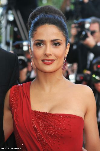Salma Hayek opts for a softer coral red lip to compliment the very rich red of her dress