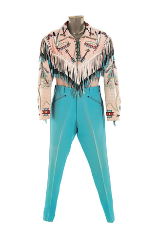 LOT-81 NUDIE THE RODEO TAILOR A pink and turquoise gabardine ensemble made by Nudie for Roy, comprising a lace-up top with a Native American theme, embroidered headdresses on the pink, black and blue leather fringed yoke, female Native Americans embroidered on the sleeves and arrows on the pearl butt